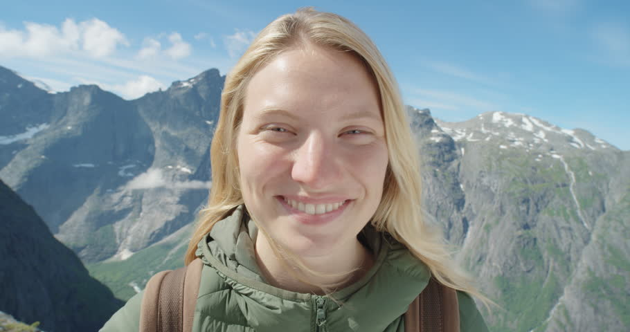 Close up portrait of Woman Climber smiling at top of mountain in nature with blonde hair blowing in wind above the clouds view Hiker Girl trekking in Norway Slow Motion | Shutterstock HD Video #25088513