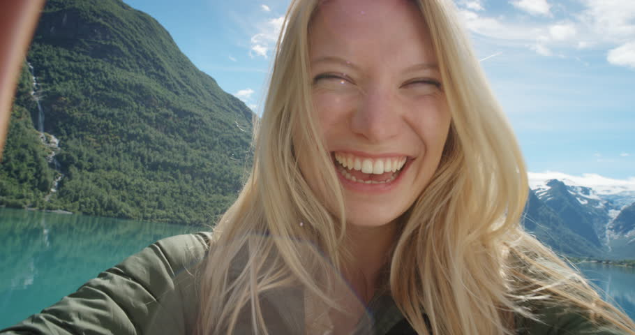 Beautiful woman having video chat using smartphone outdoors sharing travel adventure with friends Girl filming selfie video photo for social media with mobile phone enjoying Norway vacation | Shutterstock HD Video #25089635