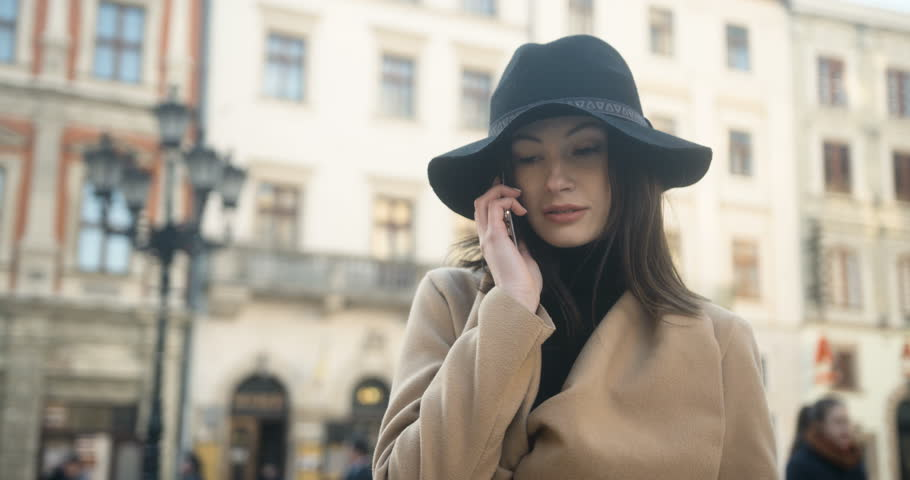Fashion young beautiful woman speaks on a mobile phone in the city on a sunny spring day, dressed in coat and hat | Shutterstock HD Video #25089689
