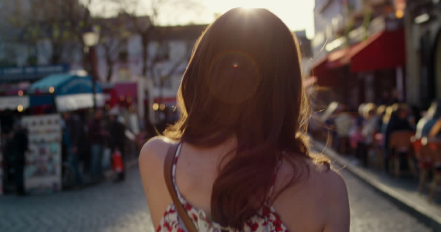 Rear view woman walking through European street at sunset wearing pretty floral summer dress sunshine lens flare confident girl exploring local Paris enjoying holiday travel vacation adventure | Shutterstock HD Video #25098509