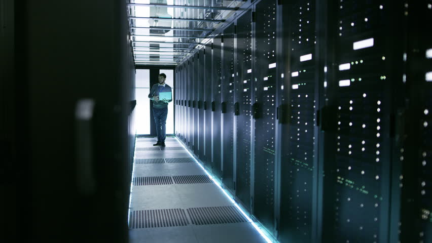 Male Server Engineer Walks with Laptop Through Working Data Center Full of Rack Servers. Shot on RED EPIC-W 8K Helium Cinema Camera.
