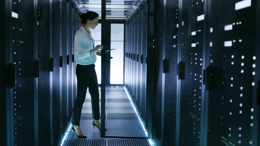 Female IT Engineer Working with Tablet in Data Center. She Closes Door of Server Cabinet. Shot on RED EPIC-W 8K Helium Cinema Camera. | Shutterstock HD Video #25116929