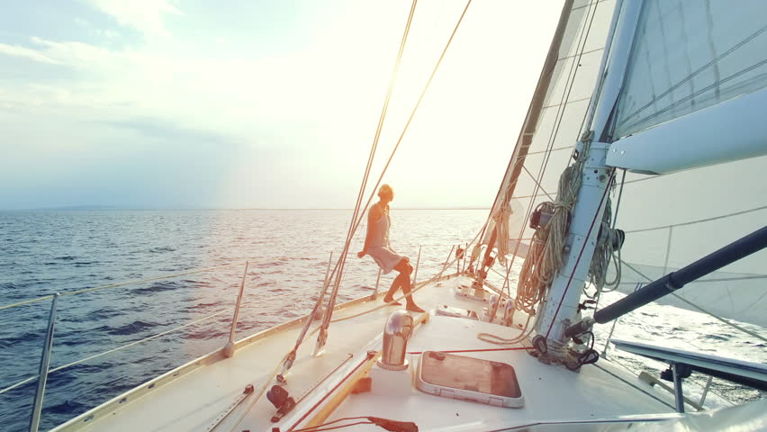 Mature adult woman is sitting on the front her big sailboat while cruising thru the ocean straight into the sunset on a sunny day on her lonely circumnavigation
