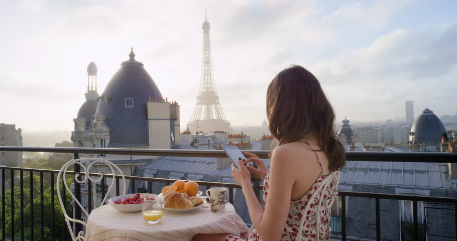 Travel woman using smartphone at Eiffel Tower Paris sharing social media view from hotel terrace breakfast vacation
