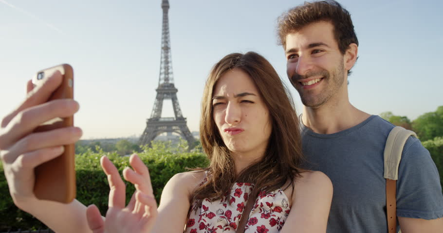 Beautiful tourist couple taking selfie using smartphone in Paris on Honeymoon enjoying European summer holiday travel vacation adventure