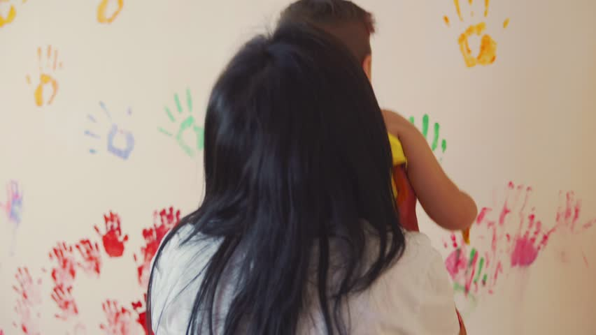 Happy mother and her cute boy having fun together leaving their colorful handprints on the wall. Mother take into arms her sun to help him to make his handprint