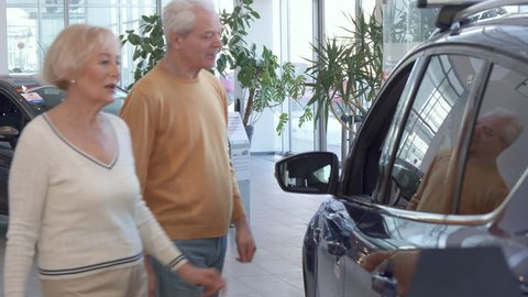 Caucasian senior couple looking inside the car at the dealership. Aged blond woman leaning her hands on the door of the vehicle. Attractive gray man standing near his wife at the showroom