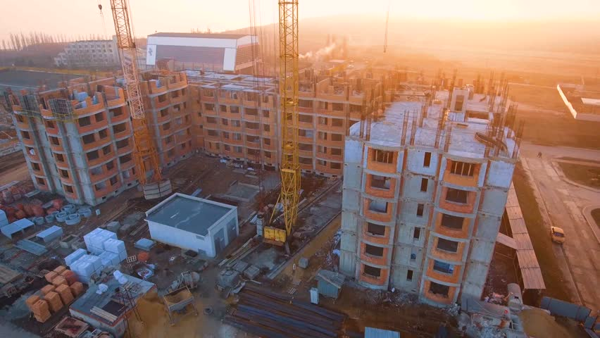 Construction site with a bird's eye on the Sunset. Video shooting with drone. Tower crane, excavator and sand. Flying over the construction site. The construction of the plant in the city.