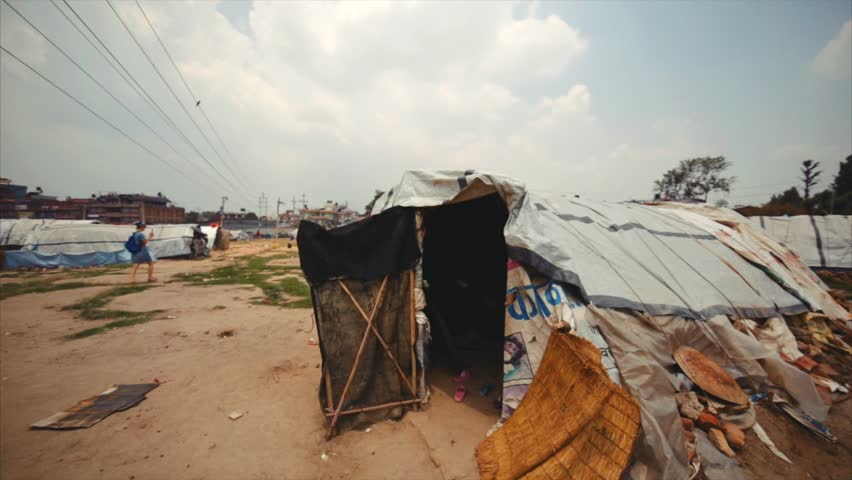 KATHMANDU, NEPAL - MAY 18, 2016: Earthquake victims camp. Woman plays witth her son in the tent. Earthquake occured on 25 April, 2015. 9000 people were killed and 22000 were injured