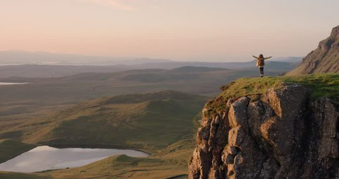 Woman with arms raised on top of mountain looking at Sunrise view Hiker Girl celebrating scenic landscape enjoying nature vacation travel adventure Quiraing Walk on the Isle of Skye in Scotland