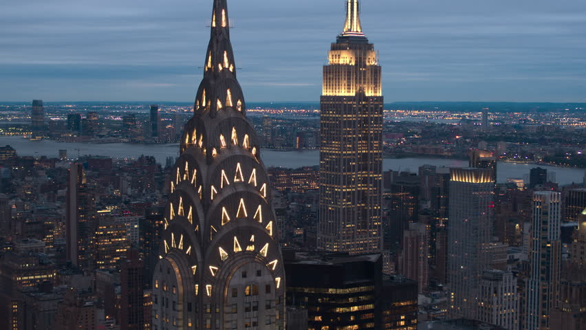 AERIAL NO VISIBLE TRADEMARKS: Flying above illuminated NYC skyscrapers in Midtown Manhattan with deleted and blurred logos on summer evening. Copyright-free New York City skyline shining at night | Shutterstock HD Video #25170419
