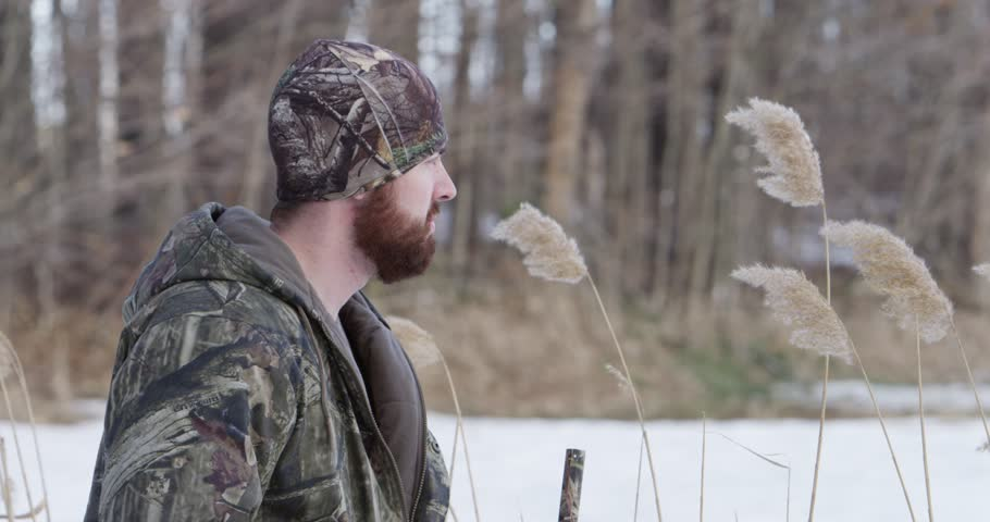 Hunter takes aim with shotgun slow motion weeds flowing in wind 4k | Shutterstock HD Video #25172909