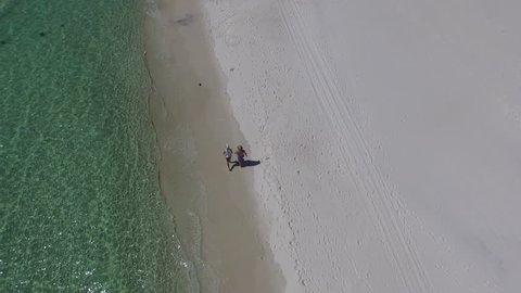 Top-down people walking the beach. drone