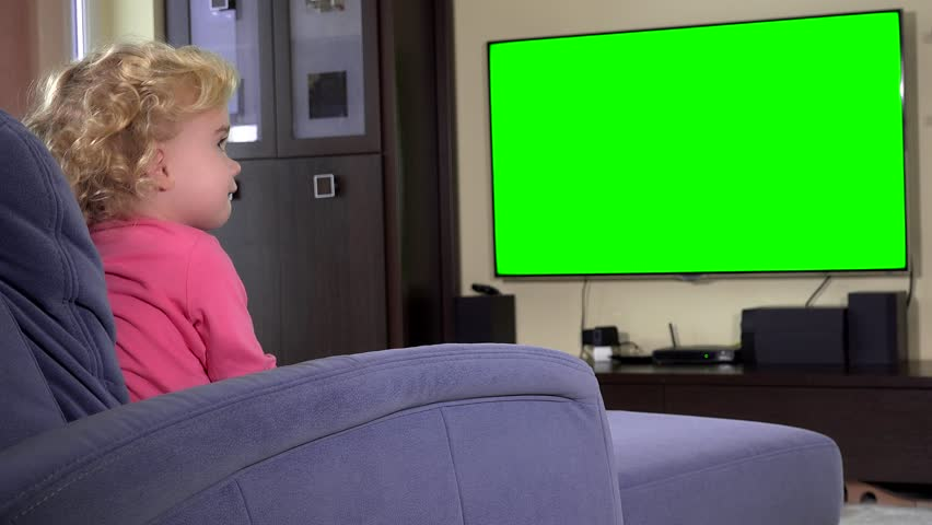 cute little girl sitting on sofa and watching tv at home. Green chroma key screen. Static closeup shot. 4K UHD