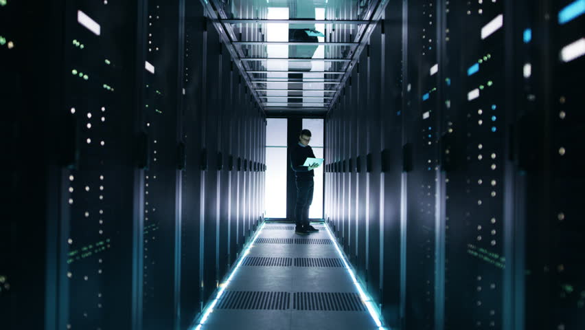 Male IT Engineer Works on a Laptop in a Big Data Center. Rows of Rack Servers are Seen. Shot on RED EPIC-W 8K Helium Cinema Camera. #25242359
