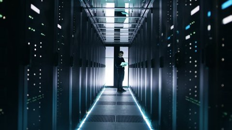 Male IT Engineer Works on a Laptop in a Big Data Center. Rows of Rack Servers are Seen. Shot on RED EPIC-W 8K Helium Cinema Camera.