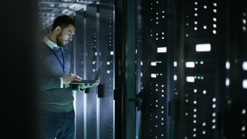Male IT Technician Working on a Laptop Standing Before Open Server Rack Cabinet in Big Dara Center. Shot on RED EPIC-W 8K Helium Cinema Camera. | Shutterstock HD Video #25243019