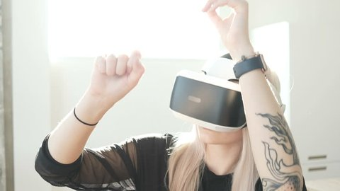 Woman using 3D virtual reality headset. Virtual reality game. Girl with pleasure uses head-mounted display. Woman wearing VR headset in living room