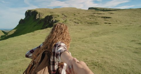 Young couple holding hands woman leading boyfriends walking towards mountain POV travel concept