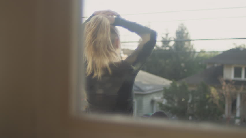 Panning shot of an athletic young woman ties her blonde hair into a ponytail while sitting on her porch, on a sunny day | Shutterstock HD Video #25254479