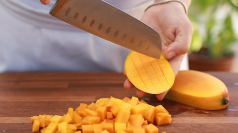 Female Chef's hands slice mango on wooden cutting board. Summer healthy vegan fruits salad on green bokeh background outdoor.