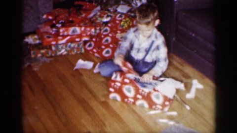 MINNESOTA 1959: a boy unwrapping a christmas gift