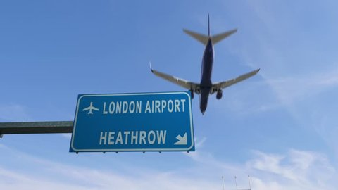 london heathrow airport sign airplane passing overhead