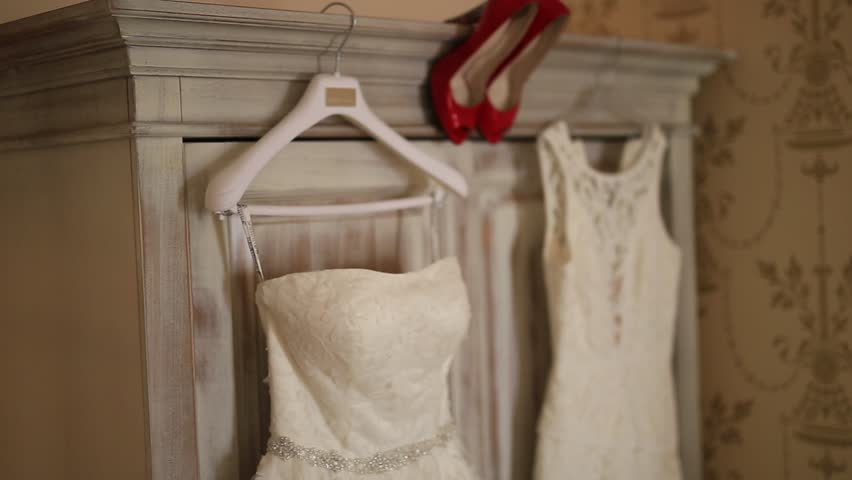 The bride s dress hangs on the hanger on the closet and the red shoes  beside her. Wedding in Montenegro. Wedding clothes of the bride. 1878a5e2e