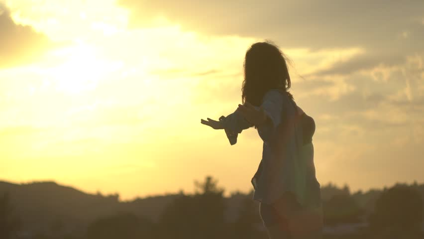 SLOW MOTION: Silhouette of a young black haired girl spreading hands and feeling the pleasant sea breeze at sunset. Feeling free and empowered.