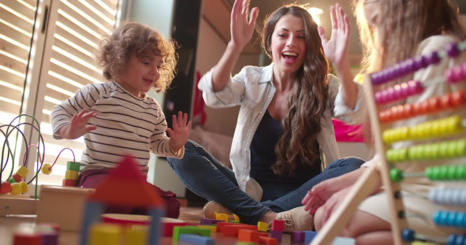 Excited boy and girl and their young aunt clapping and playing with toys