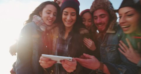 Hipster friends looking at photos online on smartphone screen on the beach during winter adventure