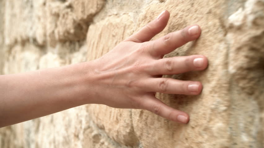 Woman's hand moving over old stone wall. Sliding along. Sensual touching. Hard stone surface.