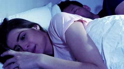 Woman cheating on sleeping husband chatting with lover on cell phone