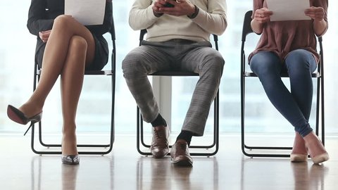 Group of three young candidates sitting on chairs in modern office, waiting and going one after another to job interview, feeling nervous. Body language. Legs close up. Job search concept. Fast motion
