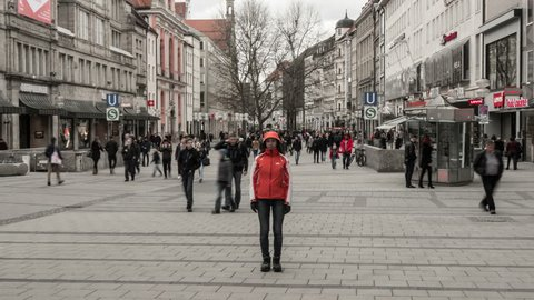 GERMANY, MUNICH - 2017 MARCH 19: Single woman standing still in the middle of the street while a crowd of people passes her by, time lapse