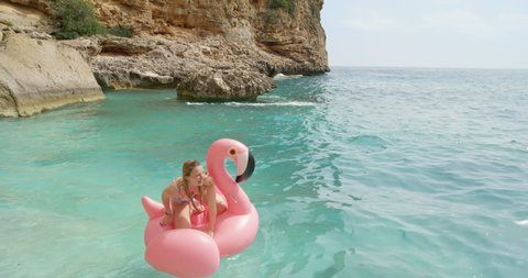 Woman lying on inflatable flamingo relaxing floating in ocean Happy girl enjoying summer vacation on tropical island holiday tanning beautiful toned beach body wearing bikini