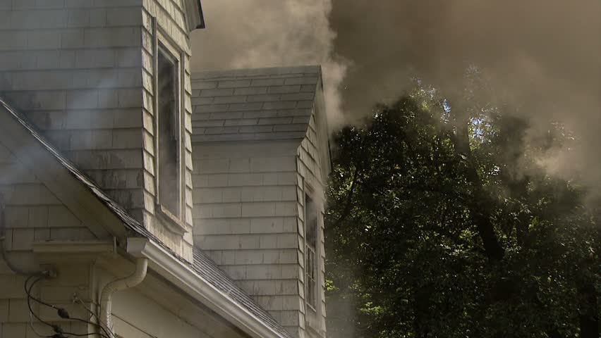 Smoke pouring out of dormers on roof of house