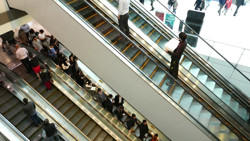 people on escalators. hong kong, march 2017 - : shopping mall crowd of people in ifc 4k on escalators e