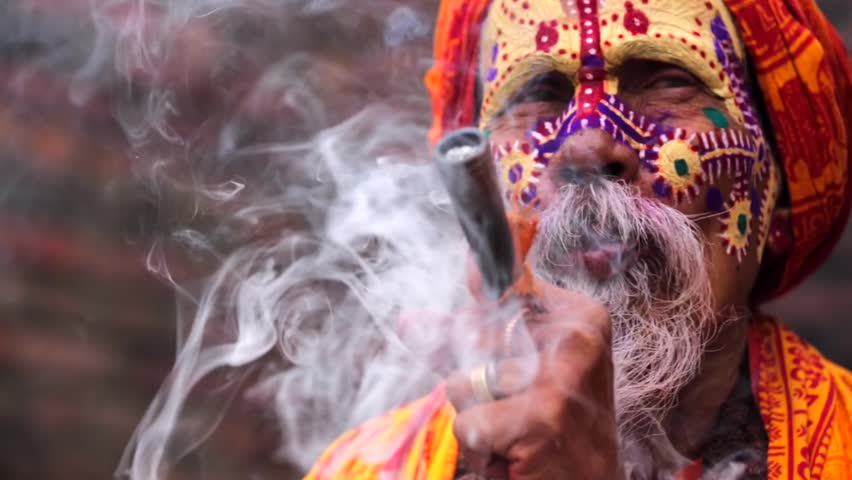 Portrait of sadhu (religious ascetic or holy person) smoking pipe with marijuana. Pashupatinath temple complex that is on UNESCO World Heritage Sites's list Since 1979. Kathmandu, Nepal.