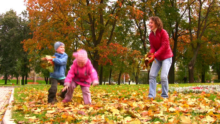 mother with children throw autumn leaves