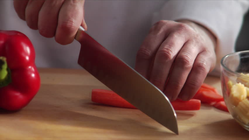 Close-up of chef chopping a carrot with red pepper on cutting board.