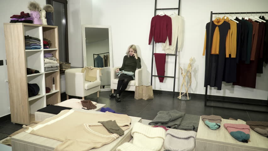 Woman talking on the phone in the boutique about the clothing | Shutterstock HD Video #25442768