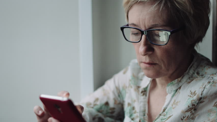 Side view shot of adult woman in glasses watching something on the smartphone screen | Shutterstock HD Video #25449995