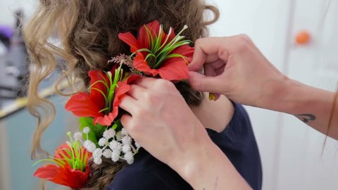 Hairstylist, hairdresser finishing creative hairstyle with flowers for teen girl in white make up room. Beauty and haircare concept