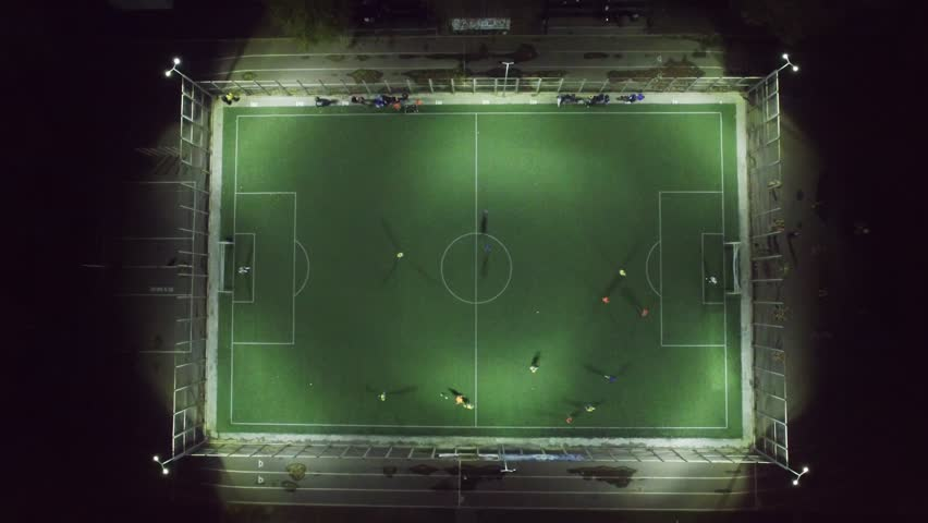 Upside down aerial view of football team practicing at night on soccer field