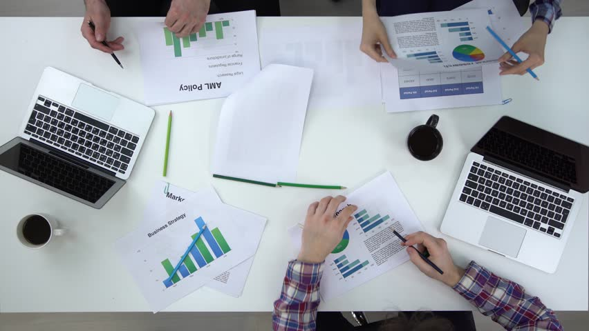 Top view of two businessmen and a businesswoman analysing graphs and writing. There are two laptops and two coffee cups on the desk. Concept of working with data. Locked down real time medium shot. | Shutterstock HD Video #25467914