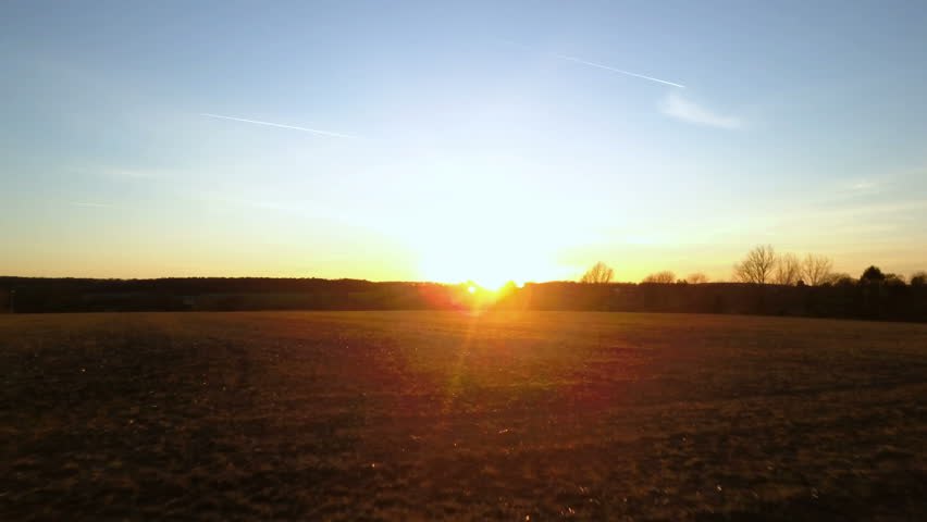 English countryside sunset. Video footage from a low-flying drone passing quickly forward over a fallow field towards the sun low on the horizon; the camera rises and slows.   Shutterstock HD Video #25506419