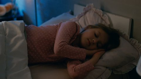 Mother Tucks in Her Cute Sleeping Girls. Shot on RED EPIC-W 8K Helium Cinema Camera.