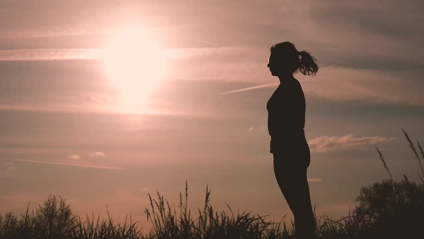 Silhouette of a girl performs some dance poses in back light during sunset in the countryside to train and take care of herself | Shutterstock HD Video #25517129