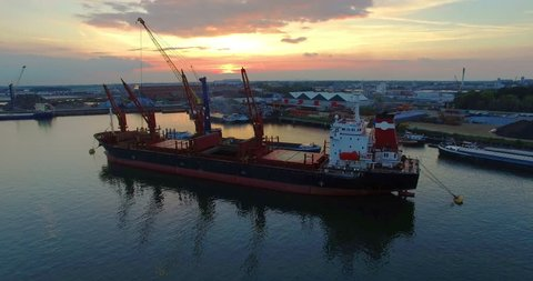Beautiful UHD Aerial video of an anchored Cargo ship in a harbor unloading cargo with a moving crane in front of a beautiful sunset. Steady ascending shot. No logo's or trademarks visible!
